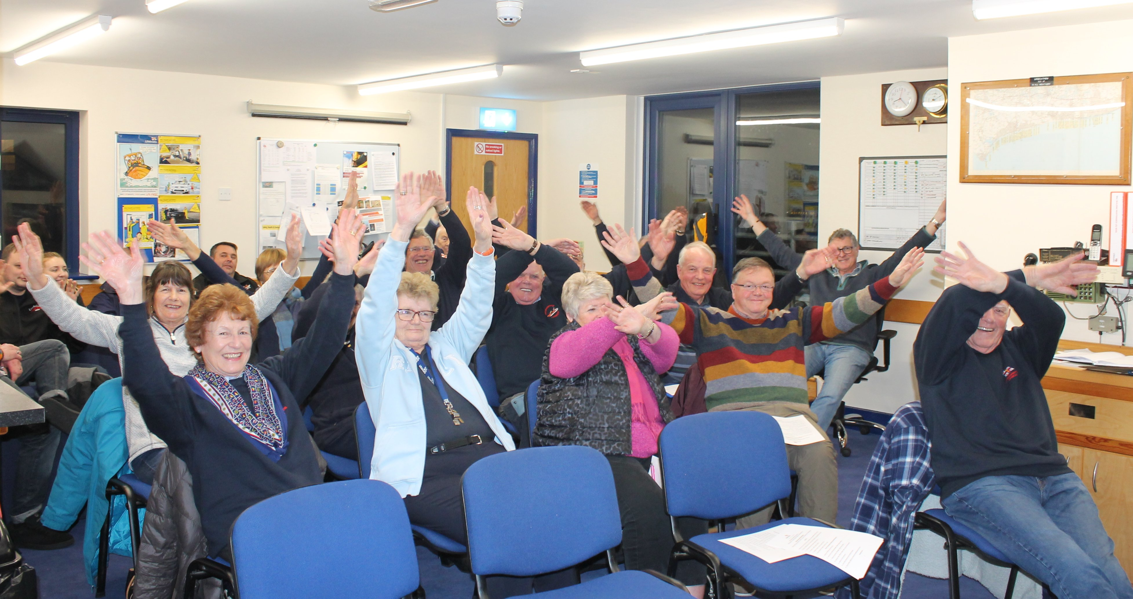 Littlehampton fundraisers demonstrate the distress signal used by sailors to catch people's attention by waving their arms in across their heads