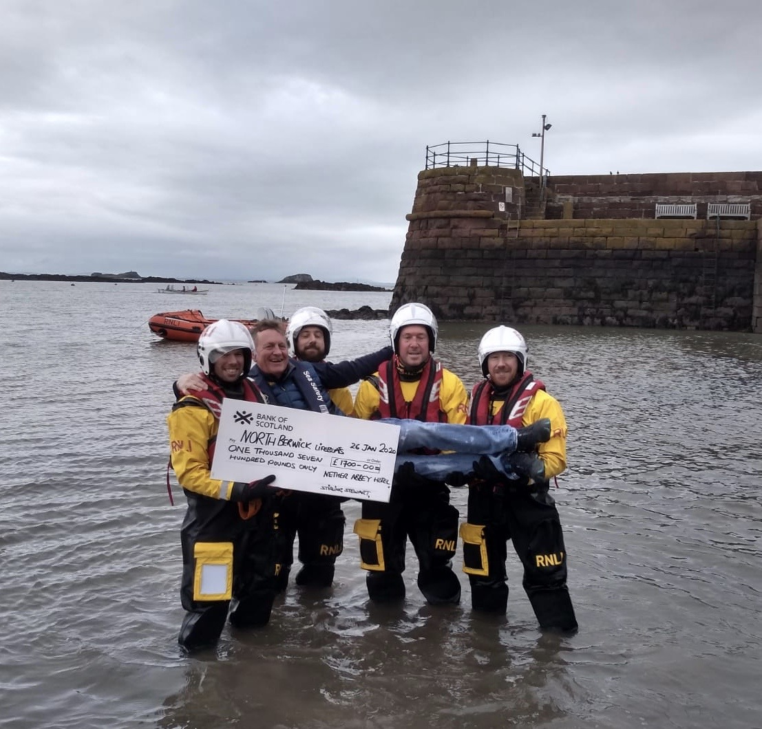 4 lifeboat crew holding Stirling Stewart handing over a cheque for £1700
