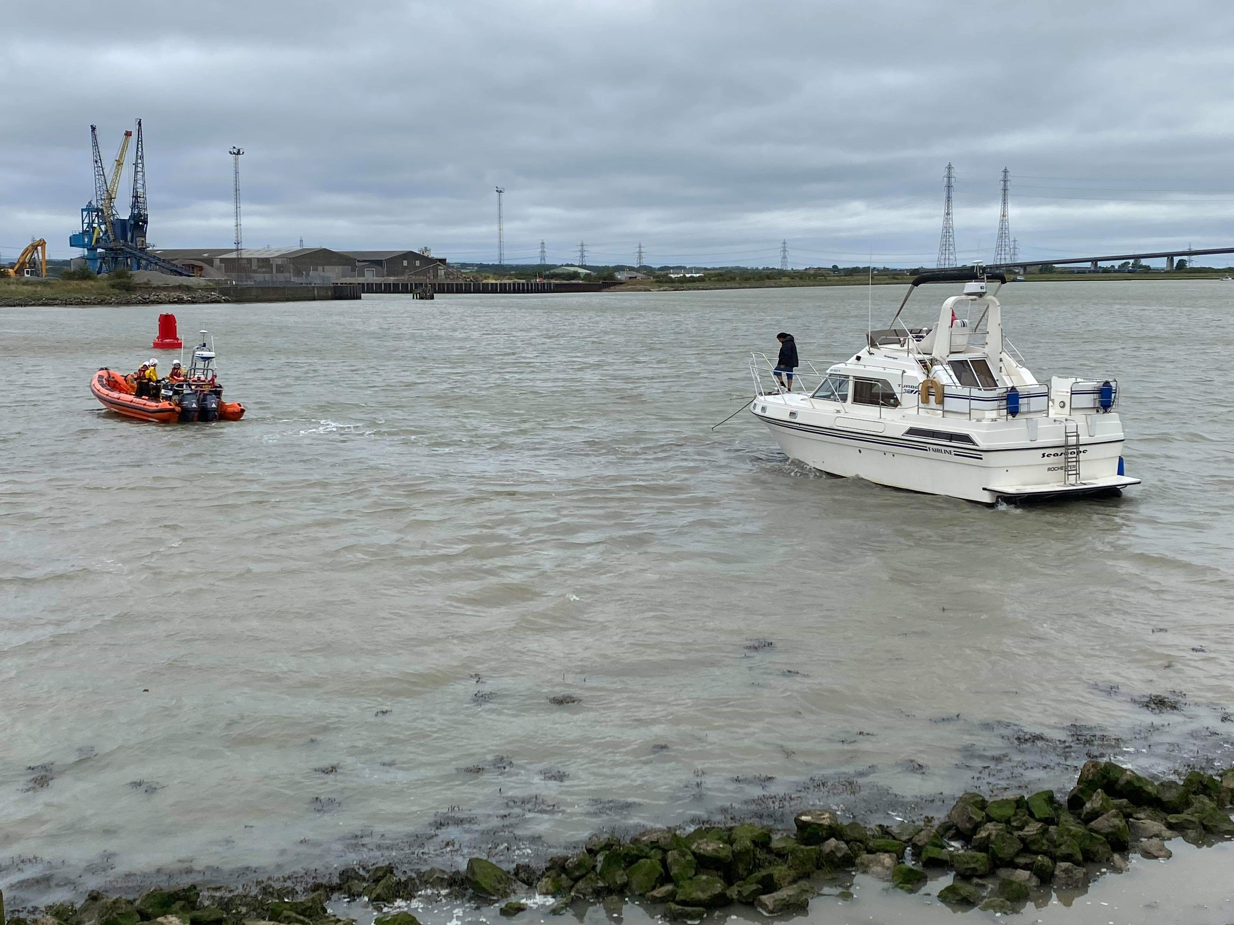 Whitstable lifeboat tows the 30-foot motor cruiser away from the sea wall on the Sheppey side of The Swale opposite Ridham Dock to a mooring after the craft got into difficulties on Friday afternoon and again on Saturday morning. Picture: James Crane/Sheppey Coastguard.