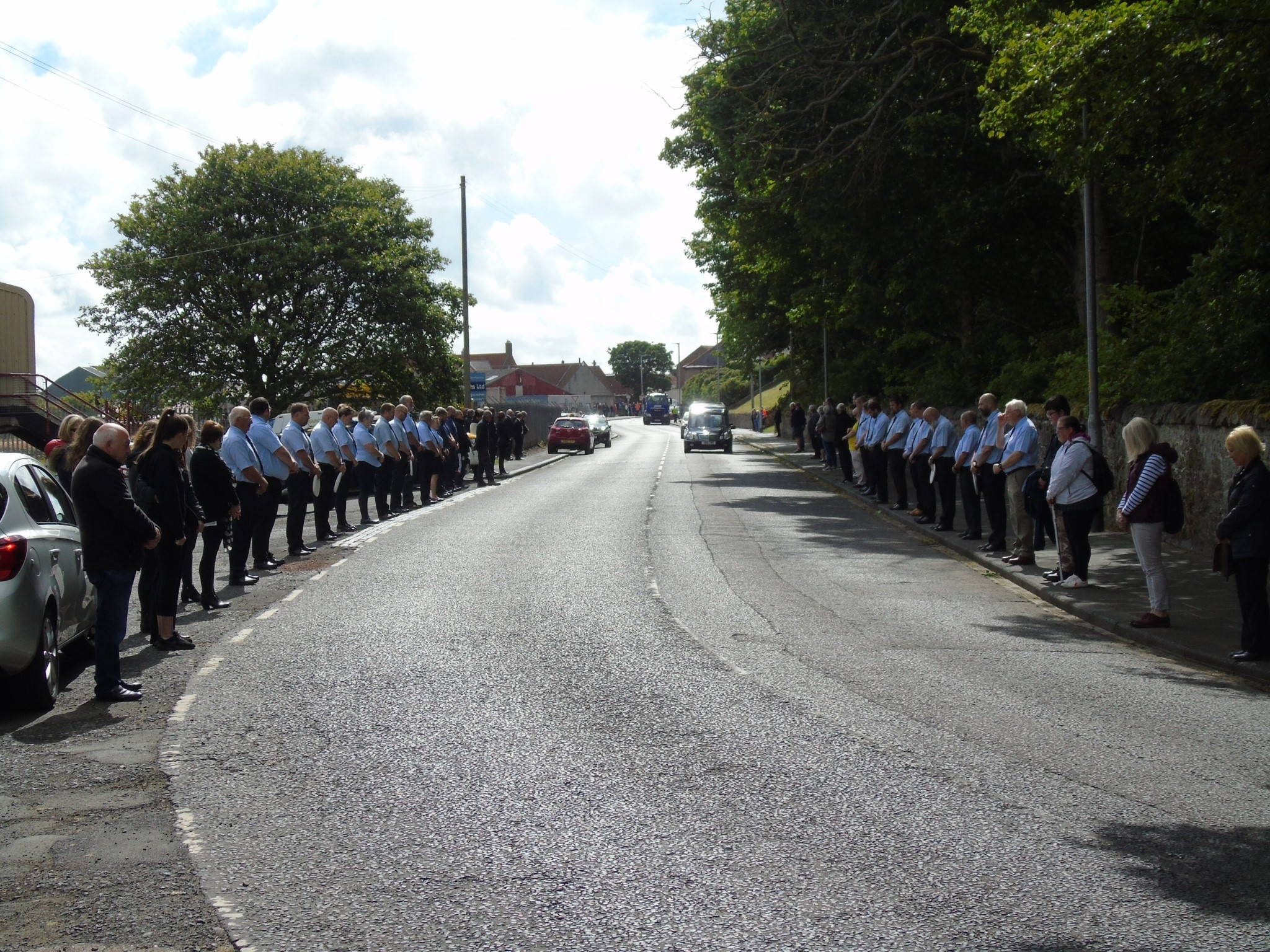 Crew line the street to say farewell to former crewman Douglas Blackhall as his hearse passes the lifeboat station.