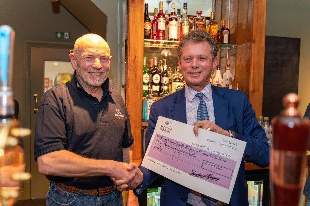 RNLI Dover Coxswain Jon Miell receives cheque from Jonathan Neame