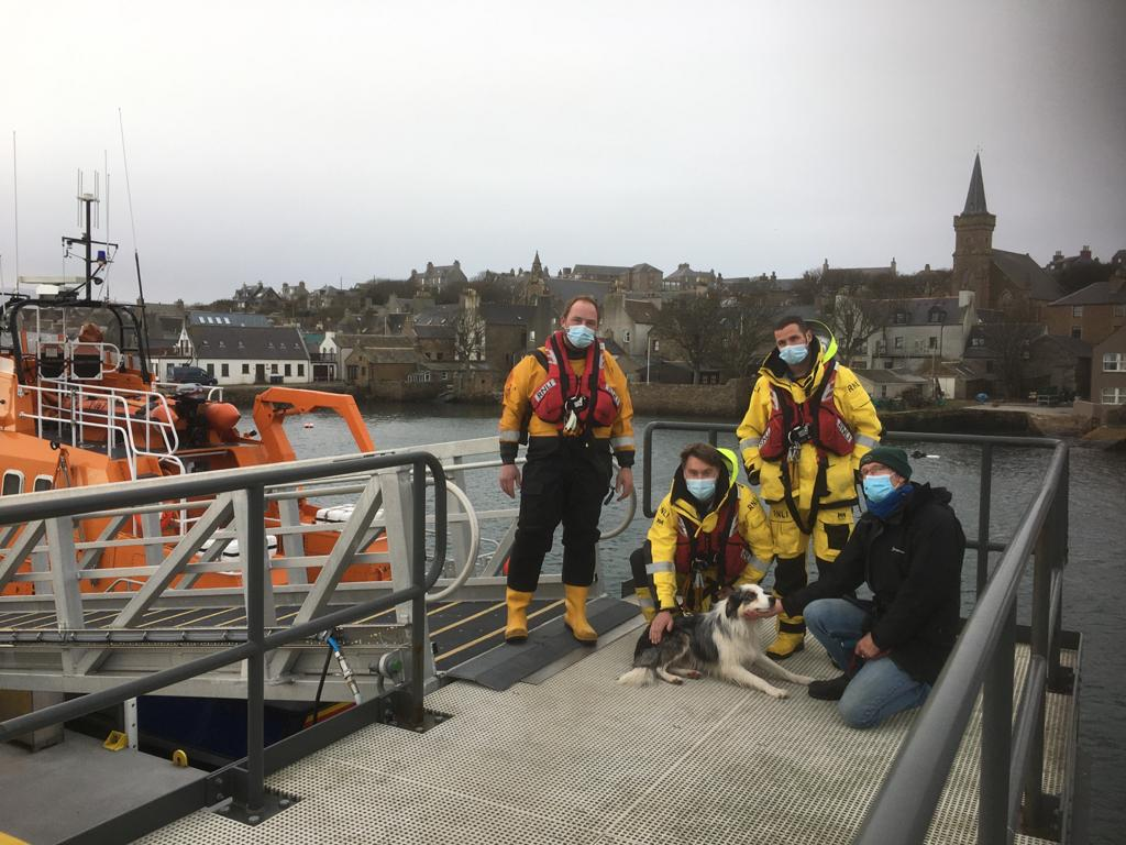 Three crew members wearing covid masks plus owner and dog on Stromness pier