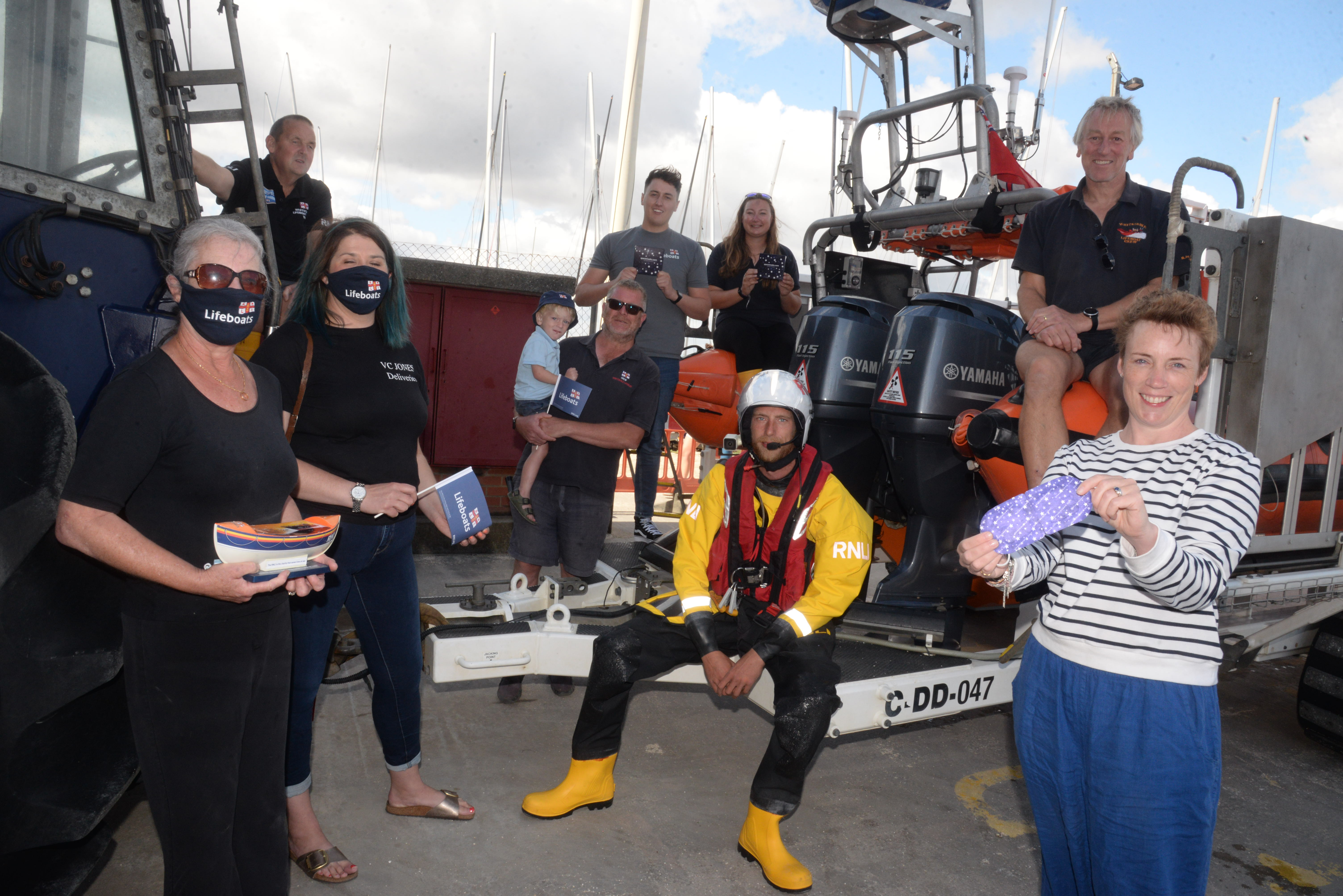 Madeleine Jones and Heather Scott of V.C. Jones with Harriet Inglis of Spacemasks with members of the Whitstable lifeboat station on Sunday.