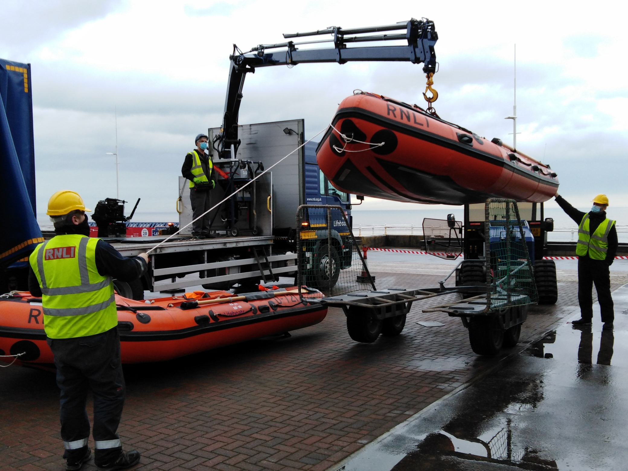 An orange inshore lifeboat is transferred from a lorry onto a tractor trailer