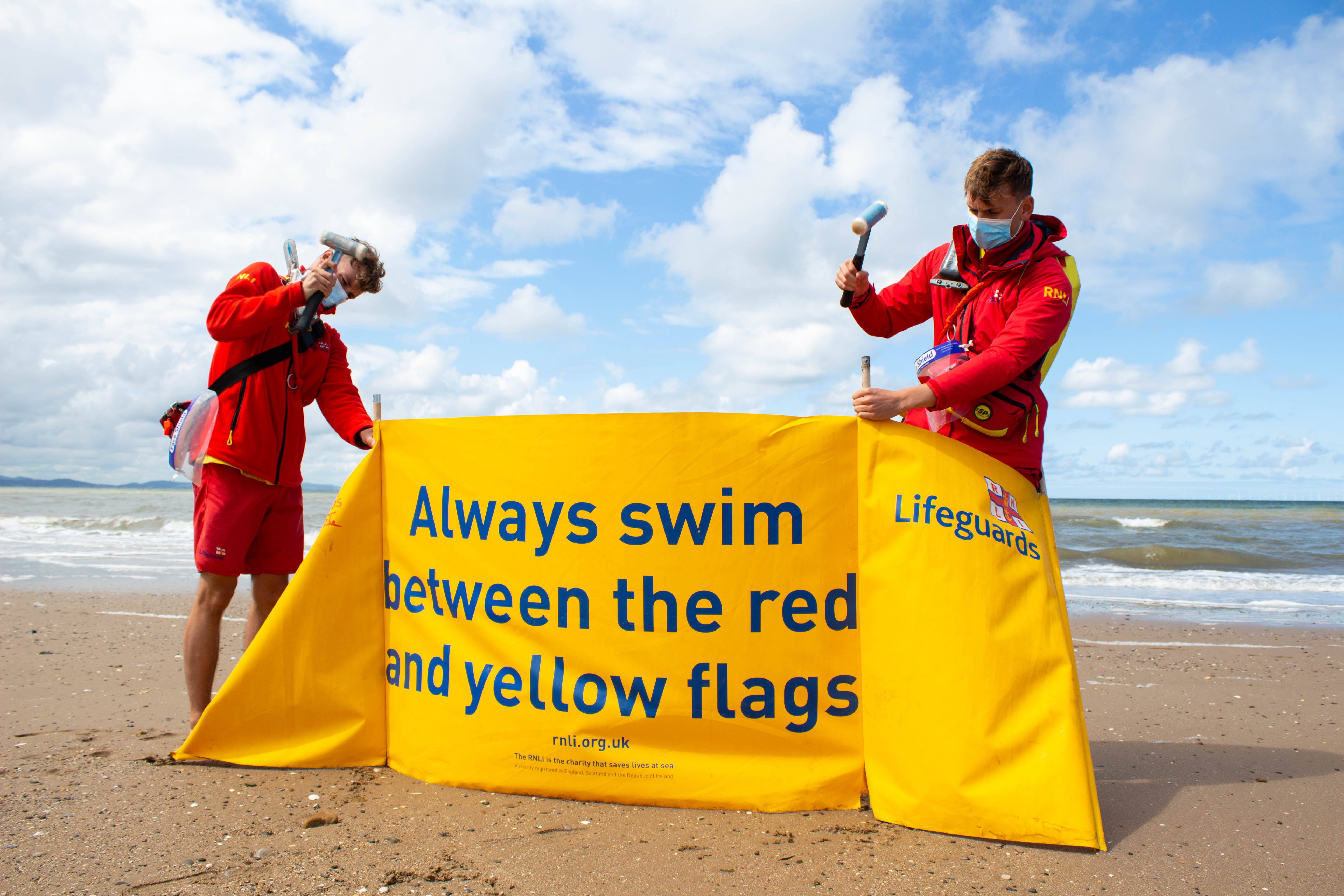 RNLI lifeguards putting up safety signage at the start of their daily patrol