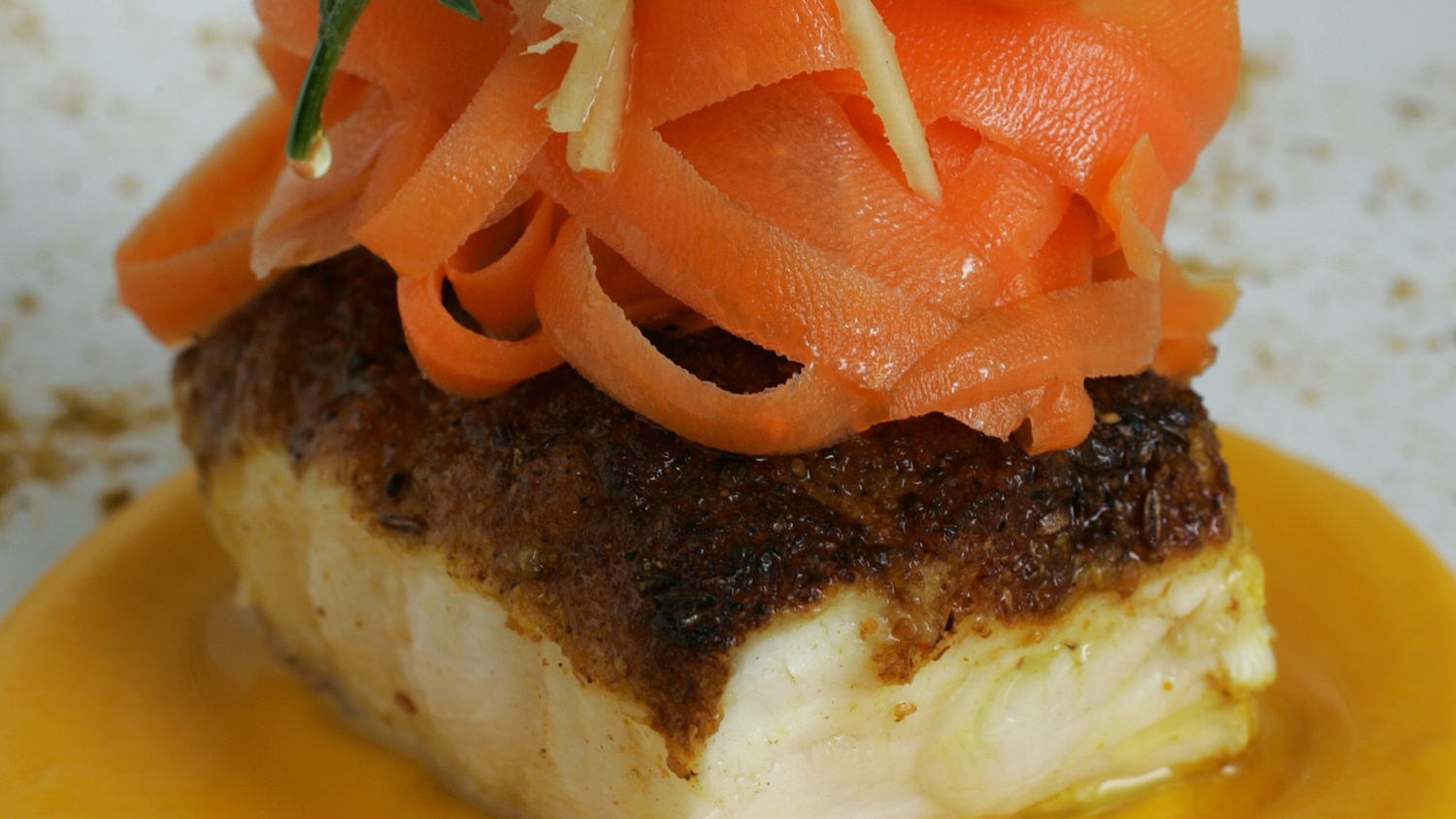 Monkfish served on a carrot and orange purée with a ginger and carrot salad