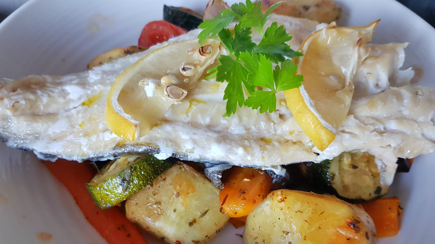Haddock served with lemon on a bed of roasted vegetables