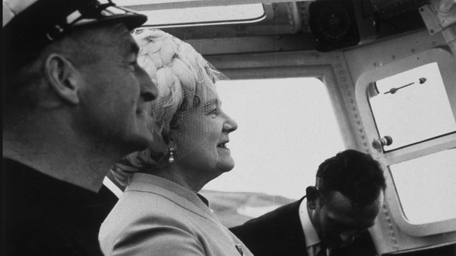 11 Aug 1971. The Queen Mother takes the wheel of Thurso's new lifeboat The Three Sisters under the guidance of Coxswain Gilbert Reid at the naming ceremony