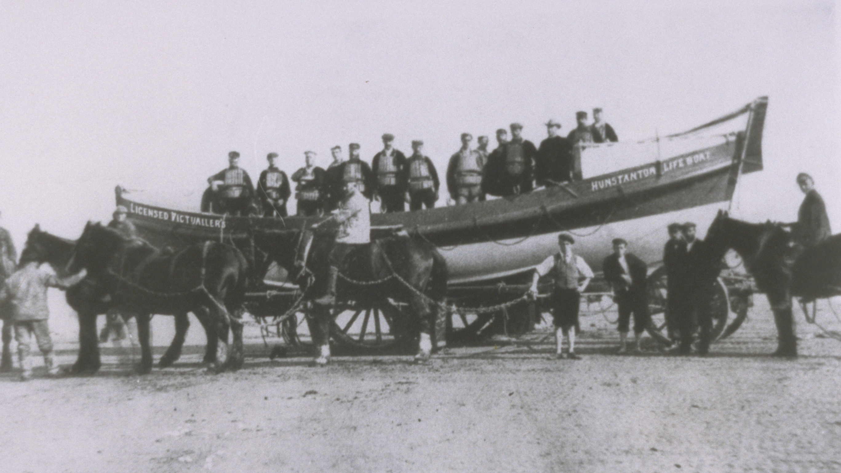 Hunstanton crew onboard their Self Righting class lifeboat, Licensed Victualler, as she sits on her horse-drawn carriage on the beach. Circa 1900-1931.