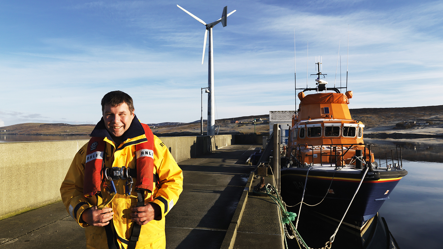 Aith RNLI Mechanic Kevin Henry with the station's Severn class lifeboat, Charles Lidbury 17-14, and wind turbine in the background