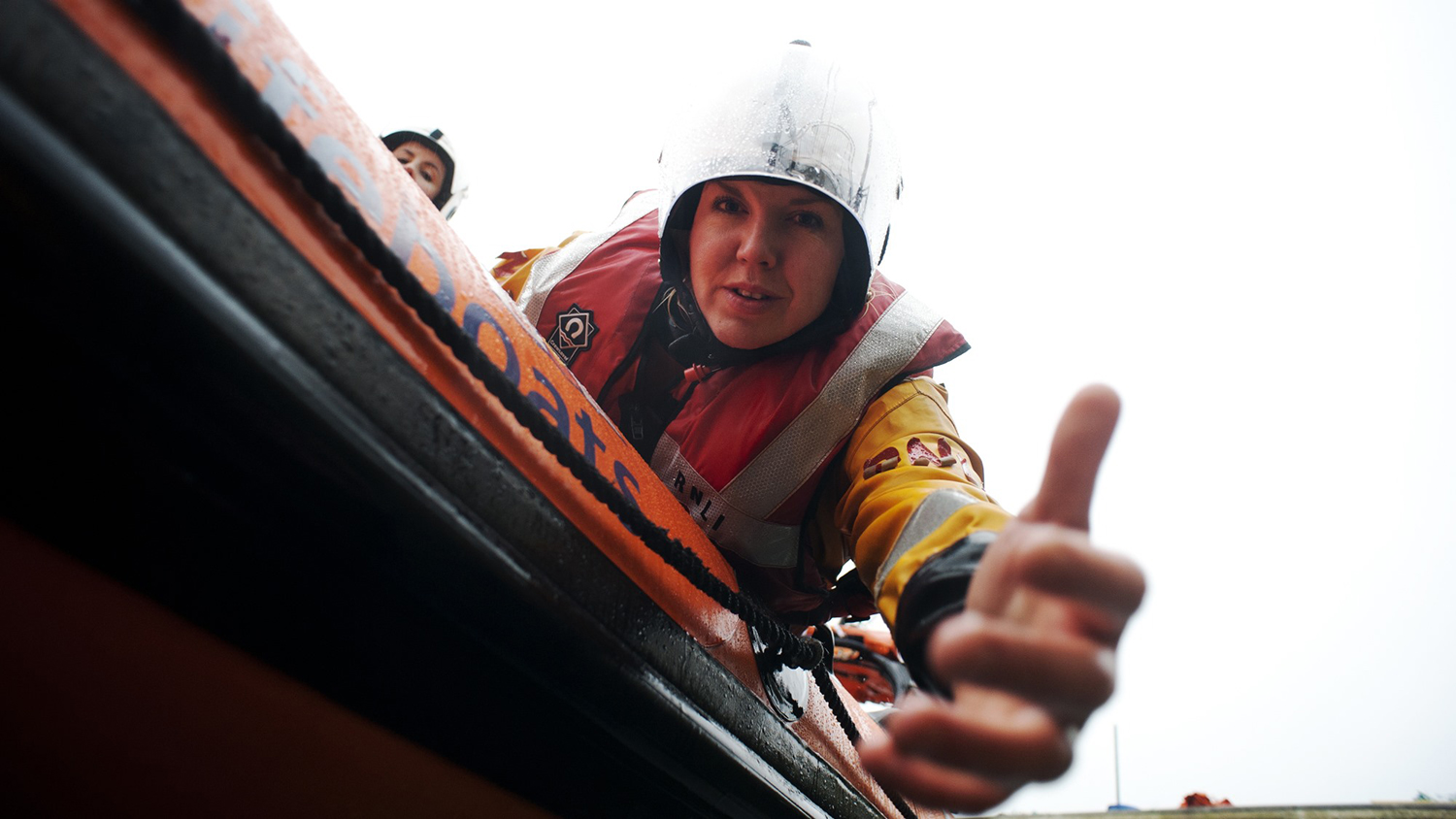 Kinsale RNLI crew member reaching out from their B class Atlantic inshore lifeboat to help a casualty