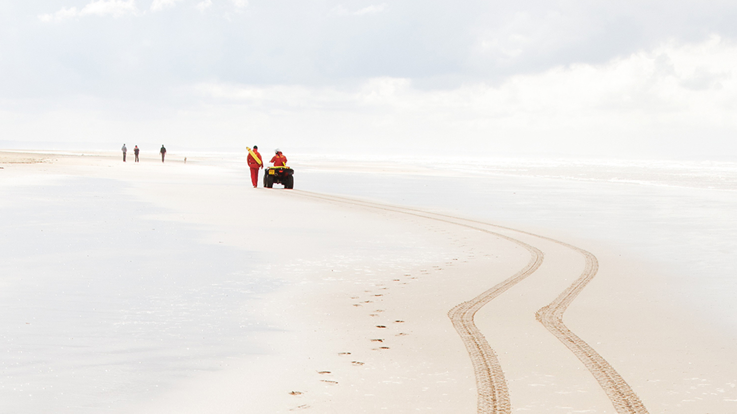 Tracks left in the wet sand by an RNLI lifeguard's all-terrain vehicle (ATV)