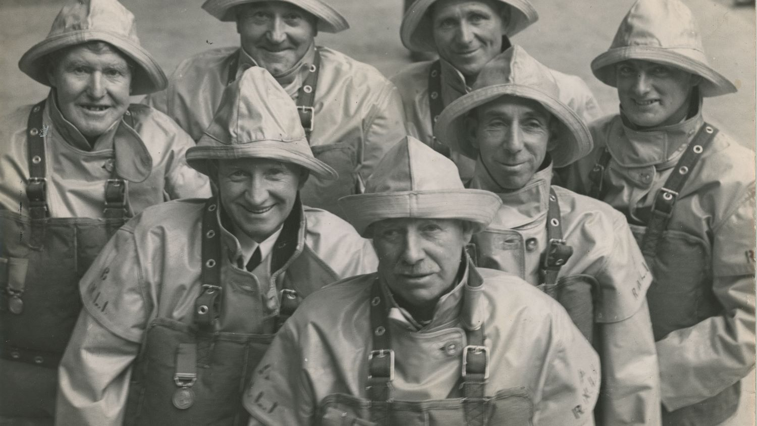 Black and white image of seven men in crew kit with medals