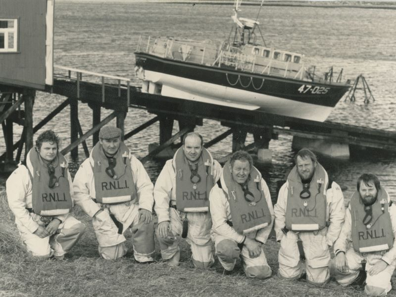 Black and white image of six crew members with lifeboat on slipway