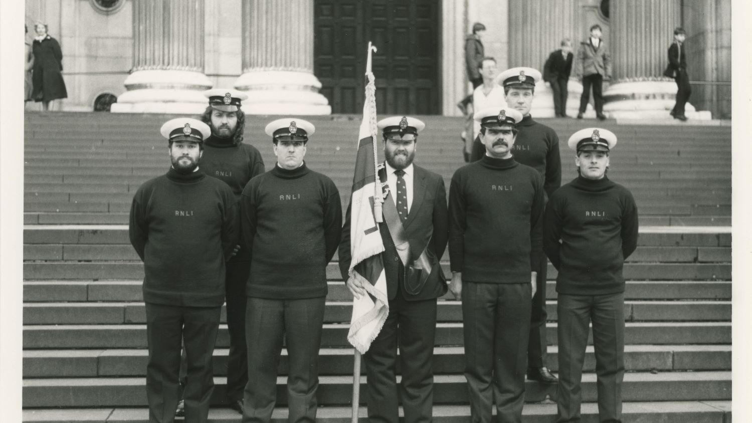 Black and white image of crew including flagbearer outside St Paul's Cathedral
