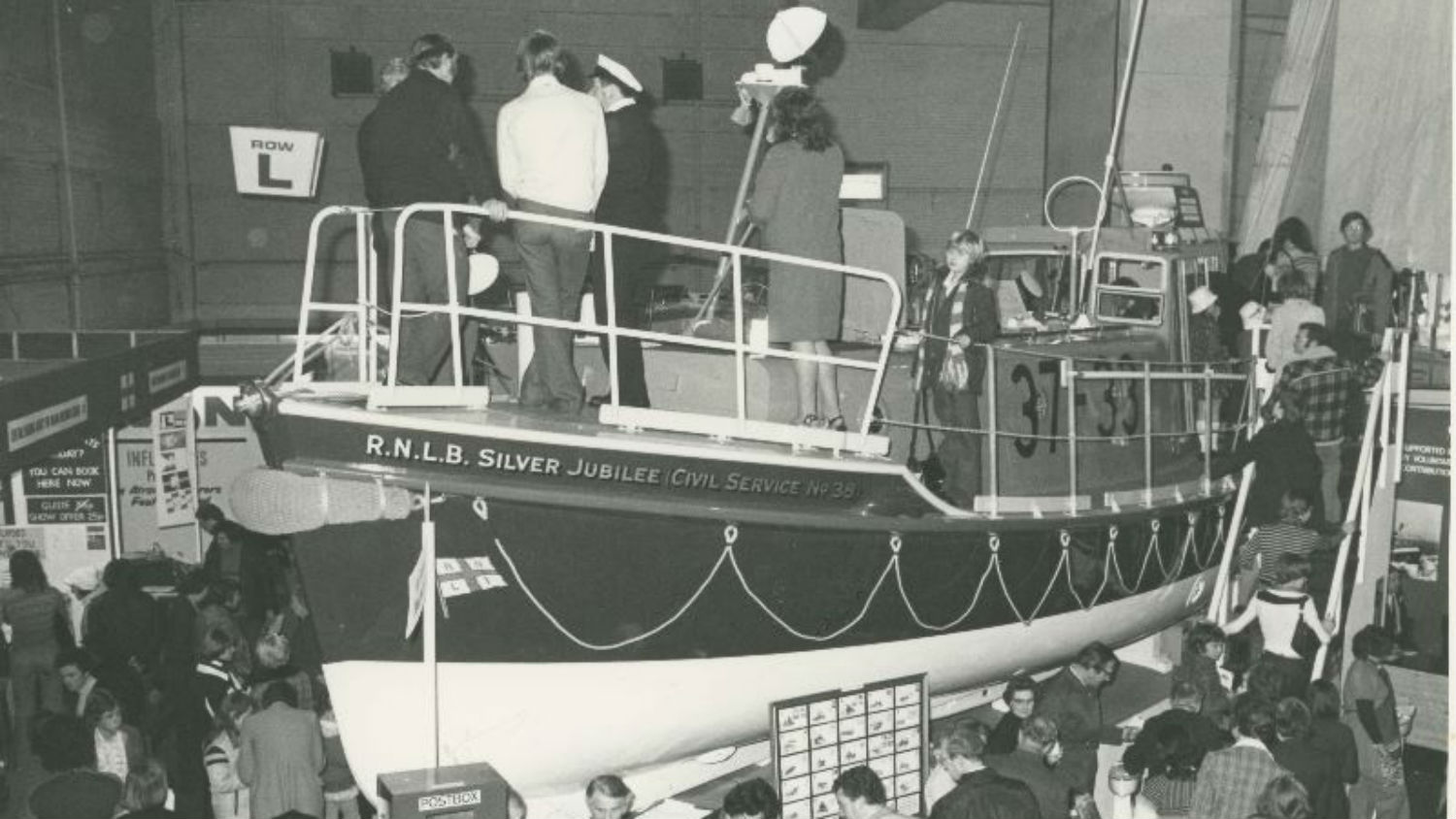 Black and white image of visitors to Boat Show viewing lifeboat