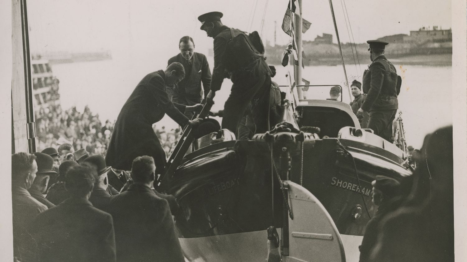 Black and white image of Prince George climbing into lifeboat at opening of Shoreham lifeboat station