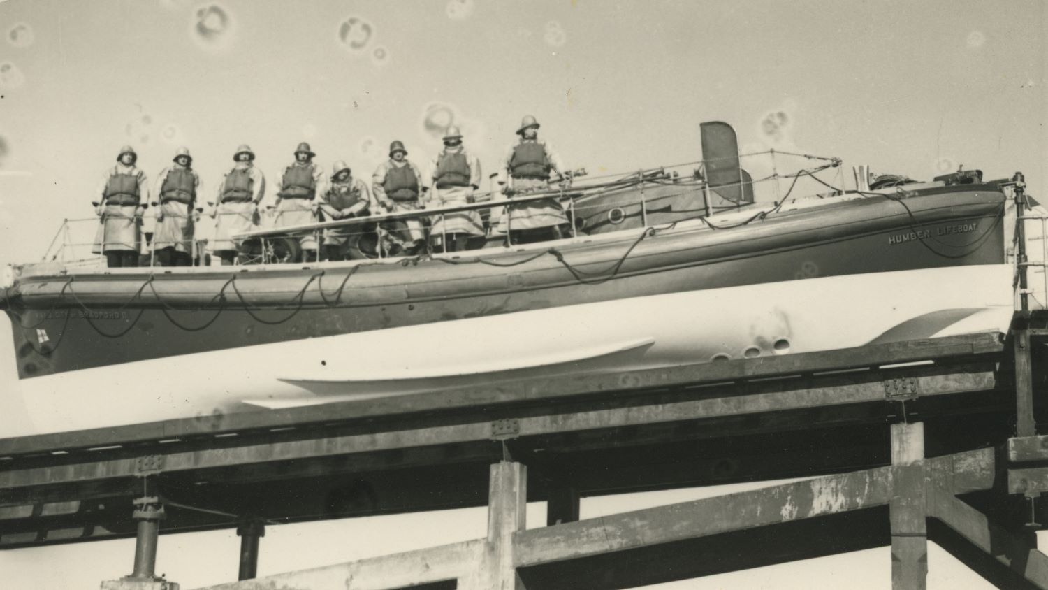 Black and white image of crew inside Humber lifeboat on slipway