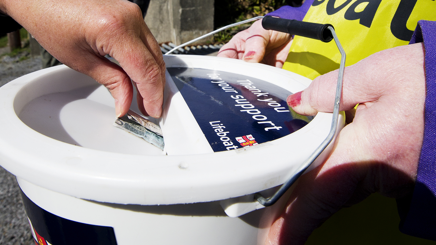 Money being donated into a collection box