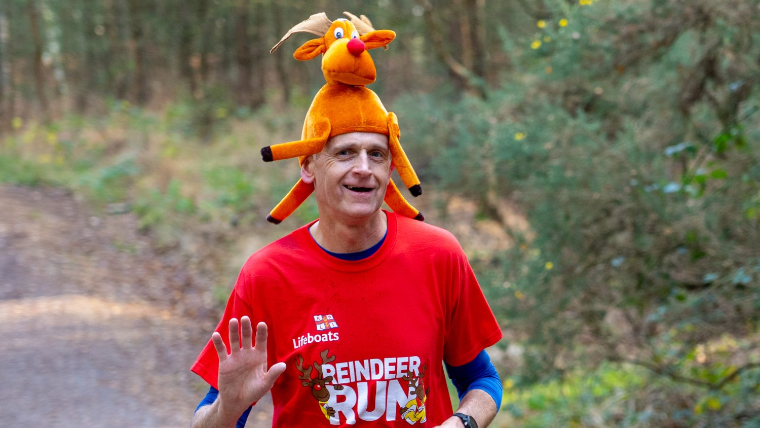 A man running the Reindeer Run in the woods wearing a reindeer-shaped hat.