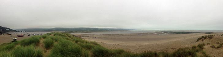 Panorama of Barmouth Beach by day: The sailors entered the water close to the harbour (left of photo), but were swept out to the open sea (right of photo).