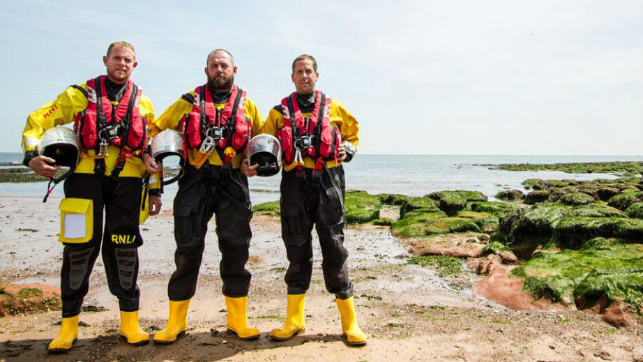 Crew members of Exmouth RNLI in full kit on the shore.