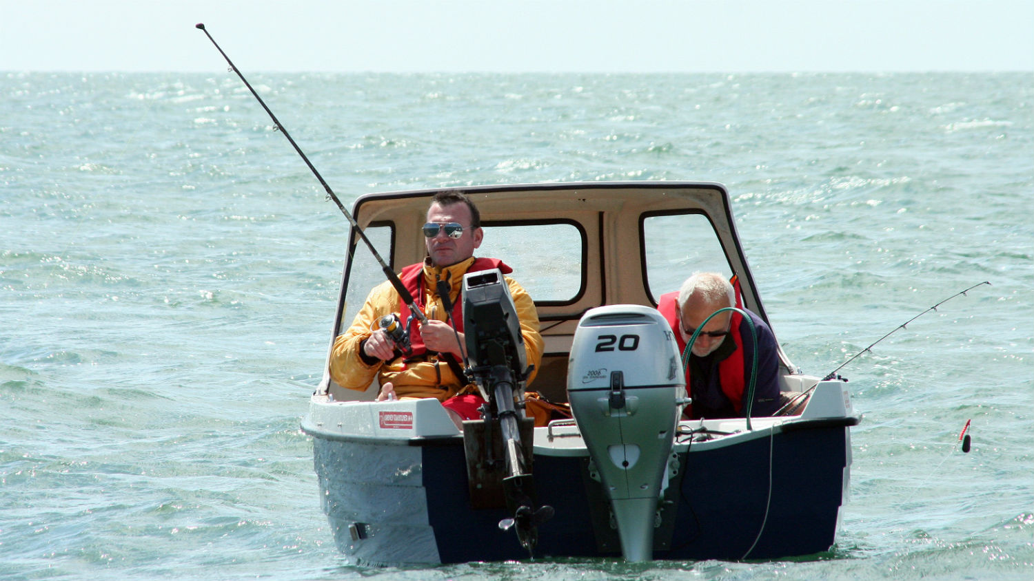 Two anglers fishing from a small boat and wearing lifejackets