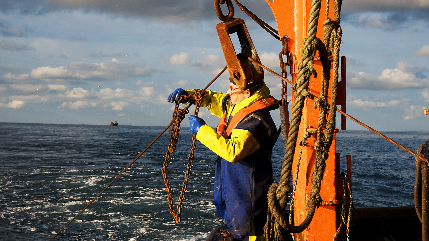 Fisherman wearing a Personal Flotation Device (PFD) while operating deck machinery