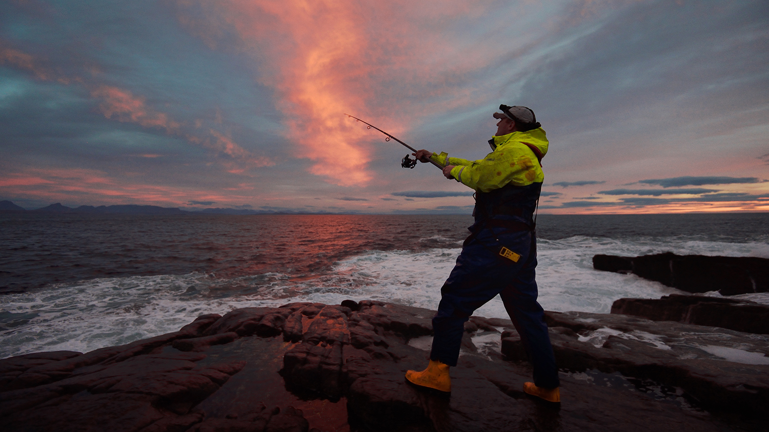 An angler fishing on rocks at sunset in Lochinver