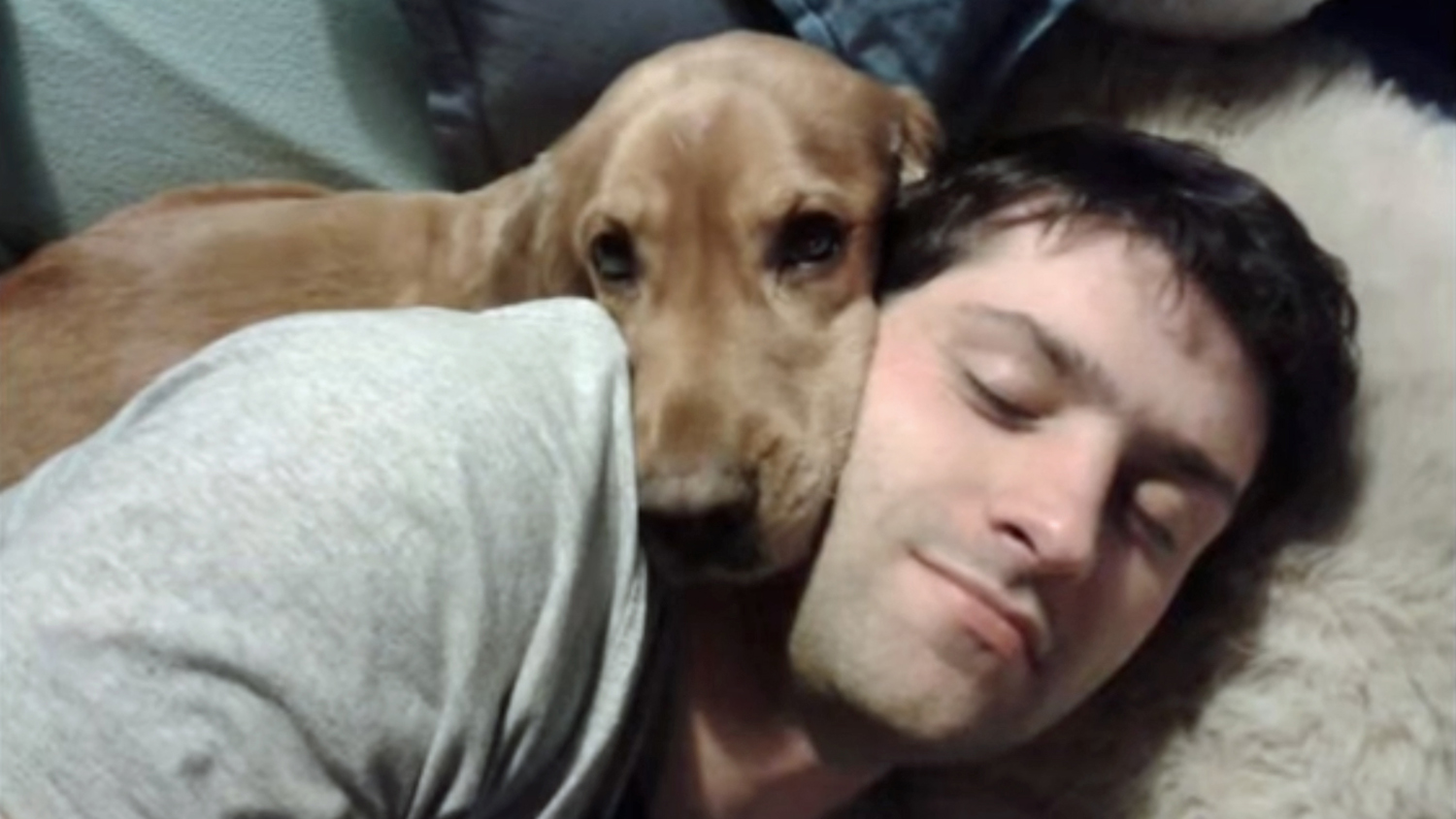 Alex snuggling with his dog