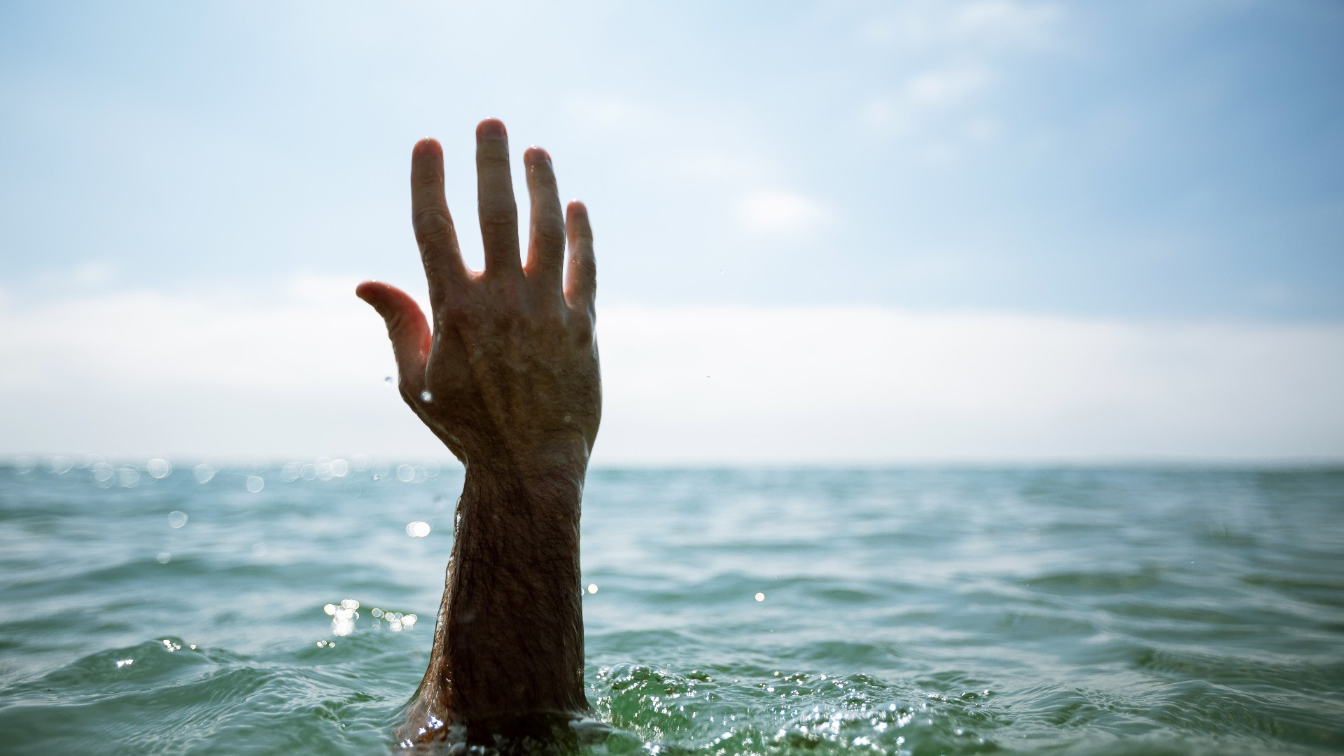 A hand is reaching up from the water
