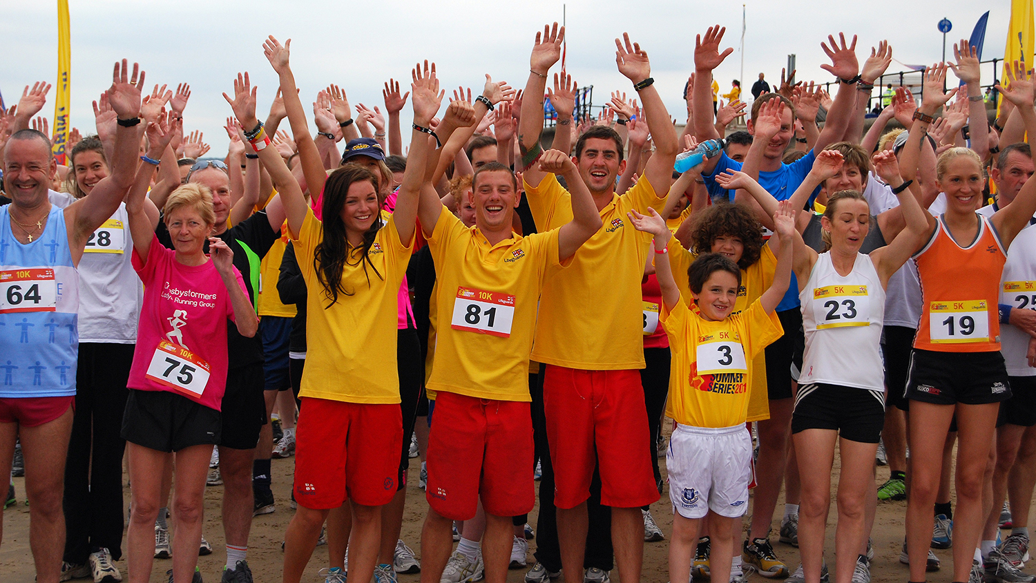 RNLI lifeguards and runners warming up at a Summer Sprint event at Crosby Beach