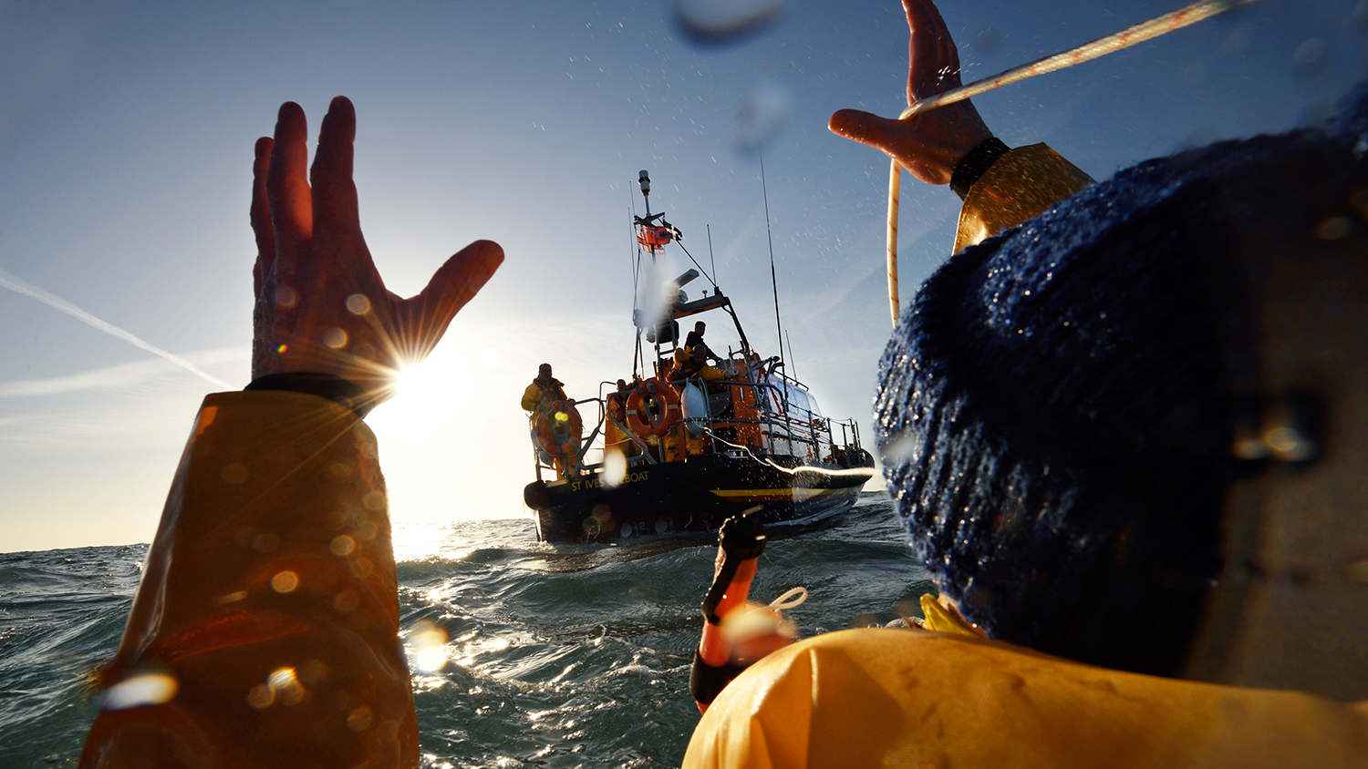 St Ives RNLI lifeboat crew throwing rope to fisherman in the water