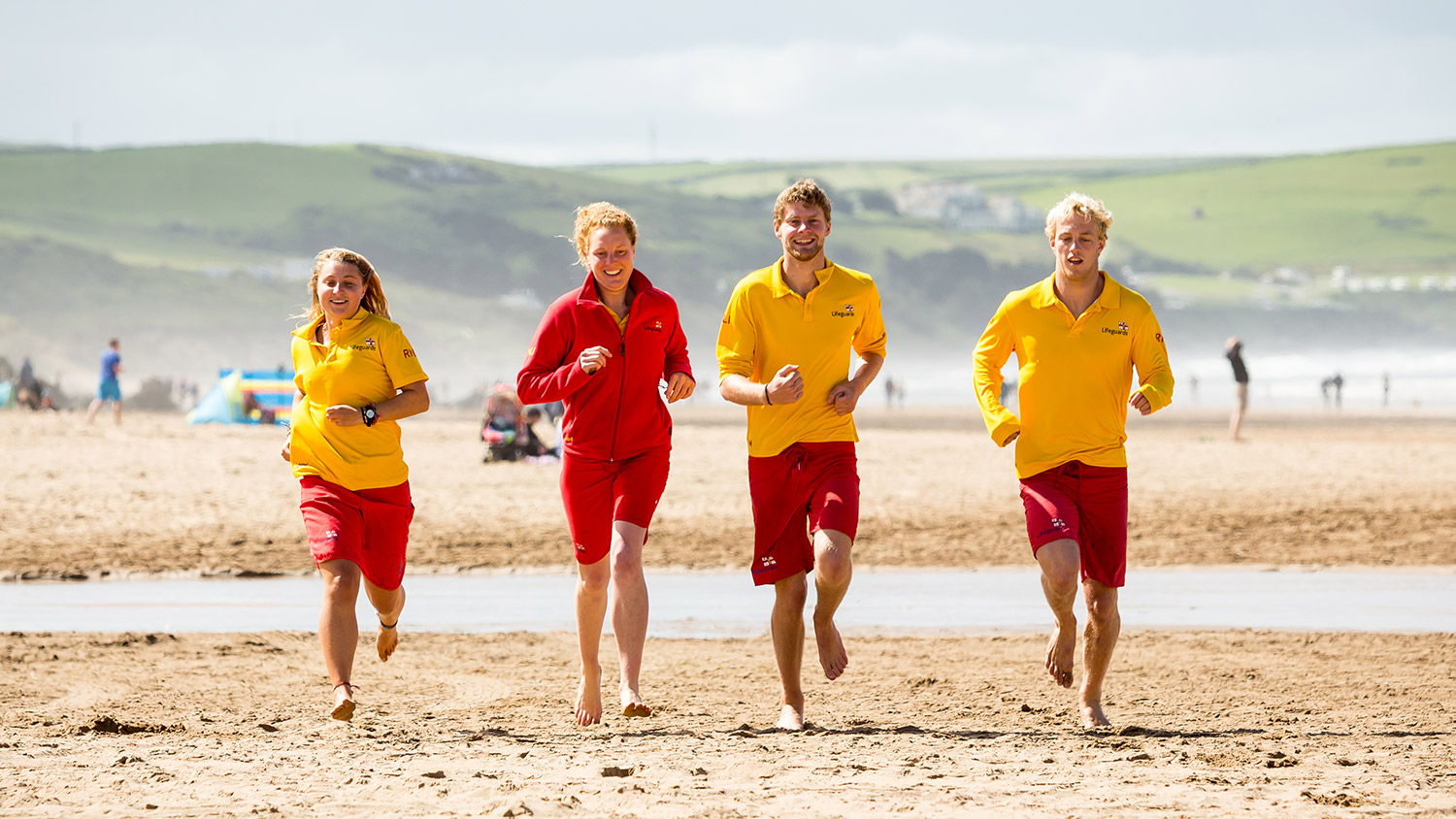 Four RNLI lifeguards running along the beach towards the camera on a sunny day