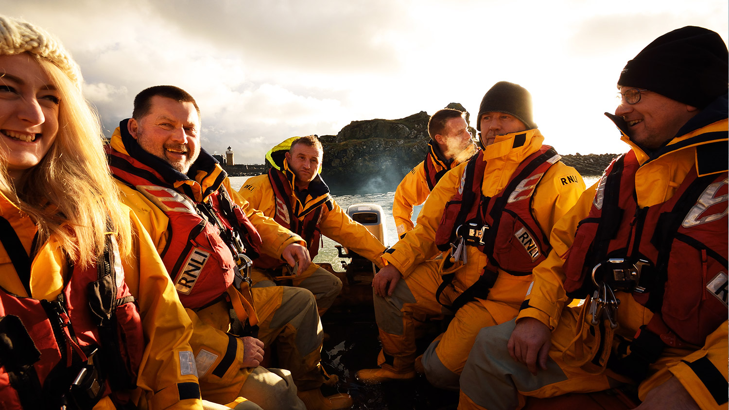 Six RNLI lifeboat crew members dressed in their all-weather lifeboat kit onboard a lifeboat