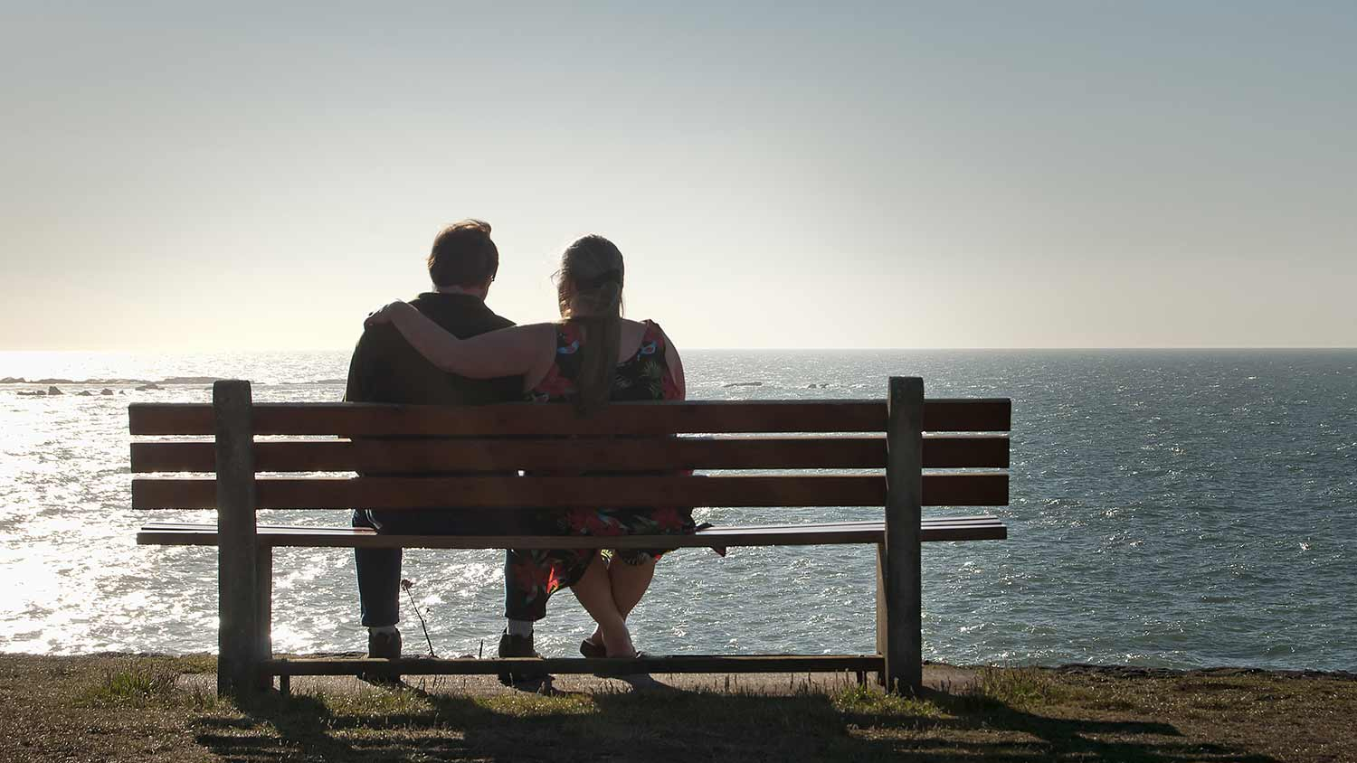 The silhouette of a couple sat on a bench looking out to sea