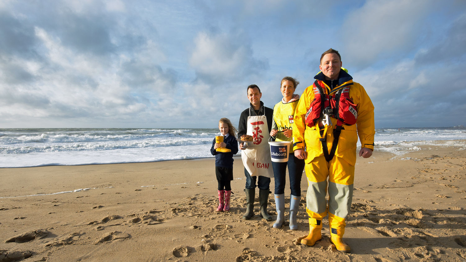 An RNLI crew member standing with three fundraisers on a sandy beach with the sea in the background