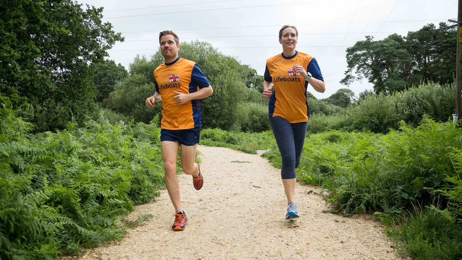 Two RNLI fundraisers running along a woodland track