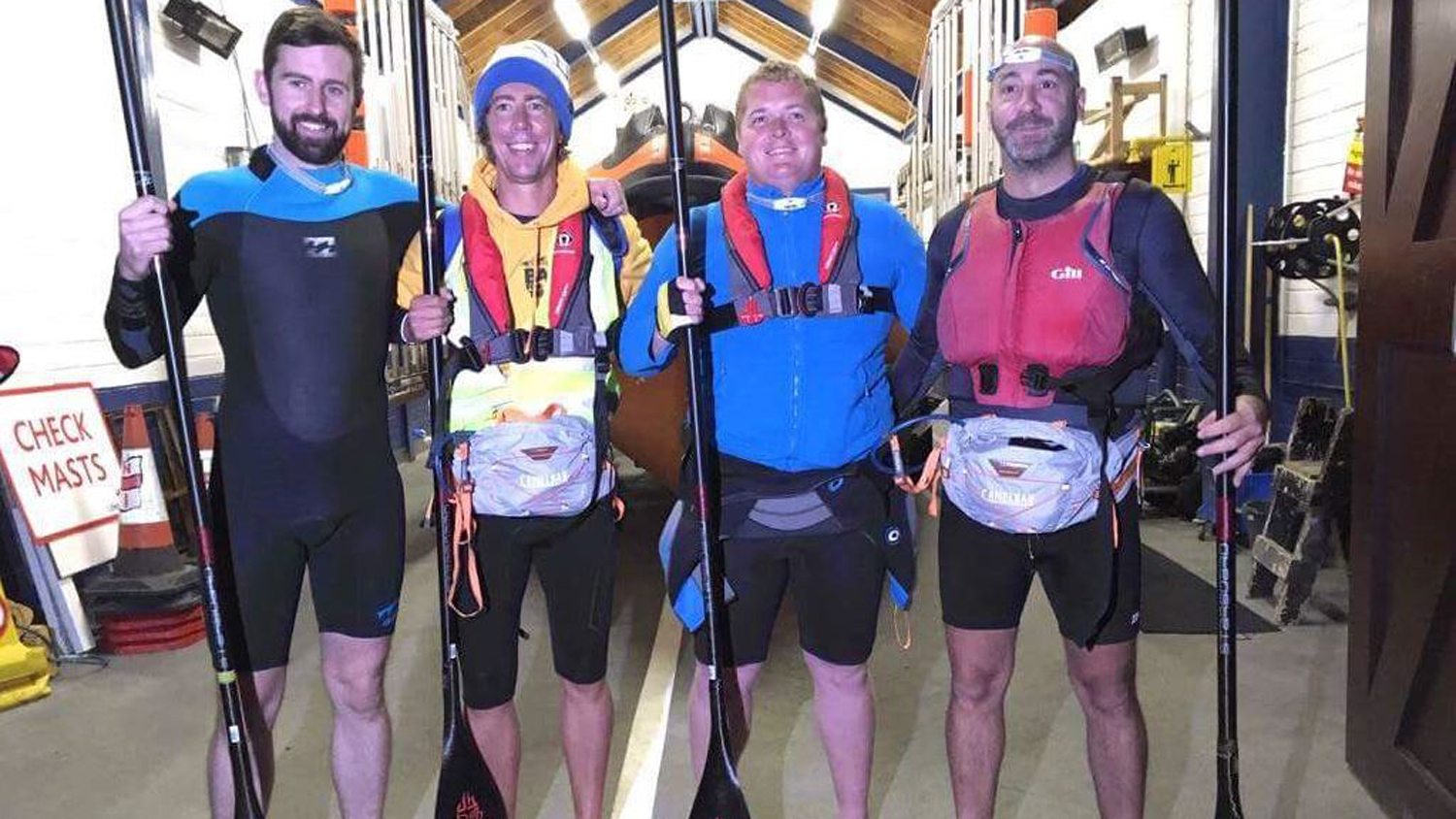 Stephen Sherwin with standing with his three SUP challenge friends in a lifeboat station