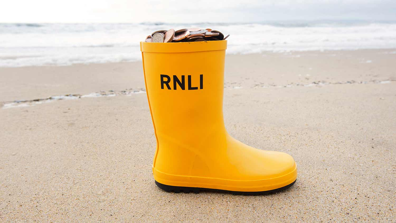 RNLI Welly filled with coins on the beach