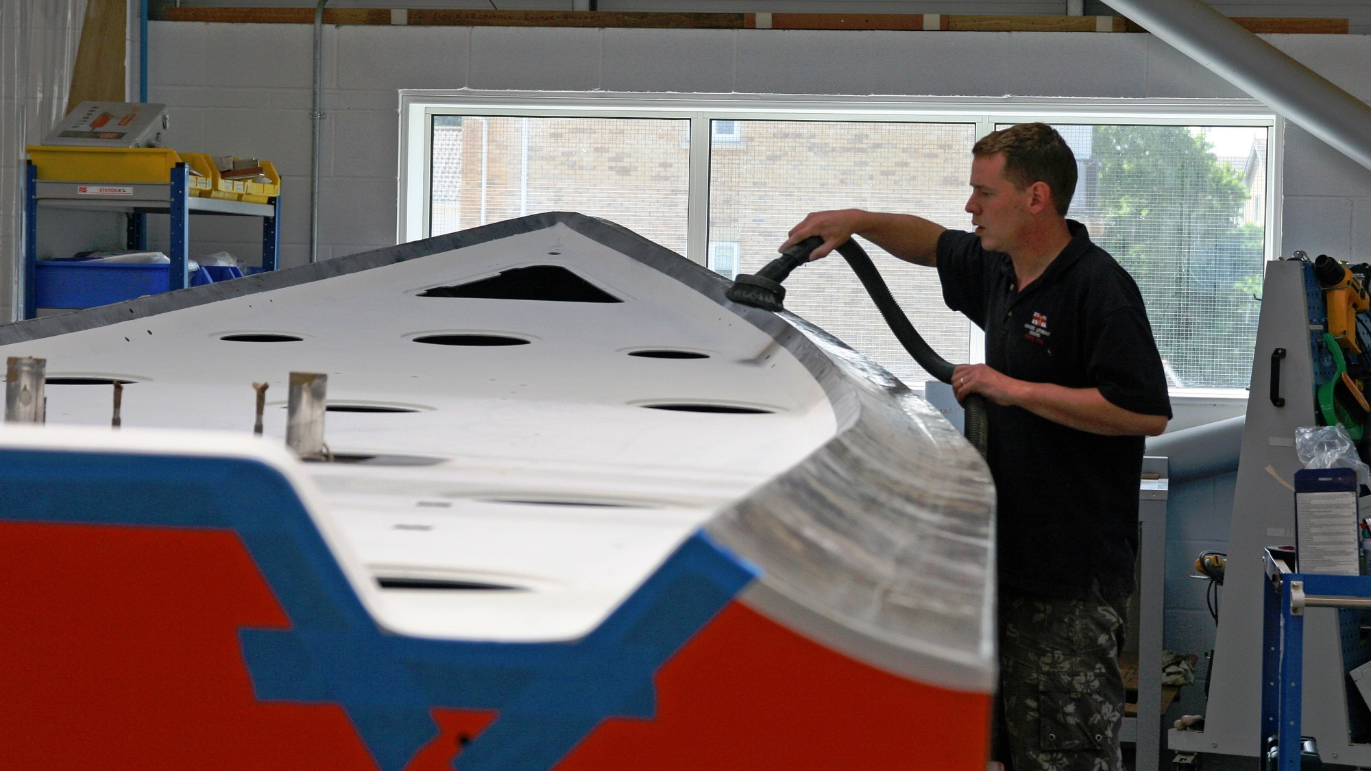 Engineer working on the hull of an inshore B class Atlantic lifeboat at the Inshore Lifeboat Centre