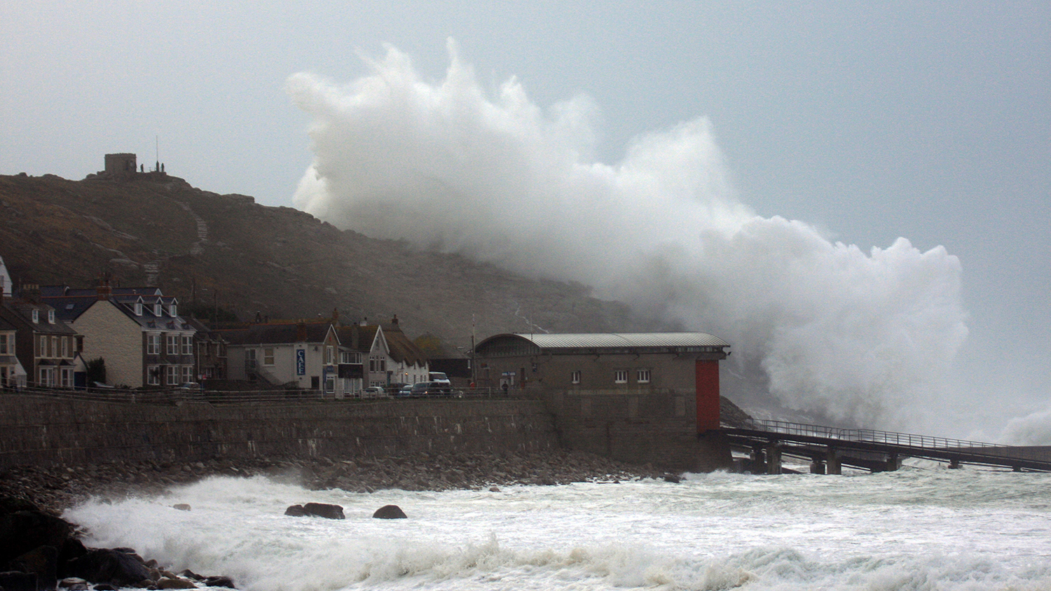 February storm at Sennen Cove with a huge wave breaking over the headland and the lifeboat station in the foreground