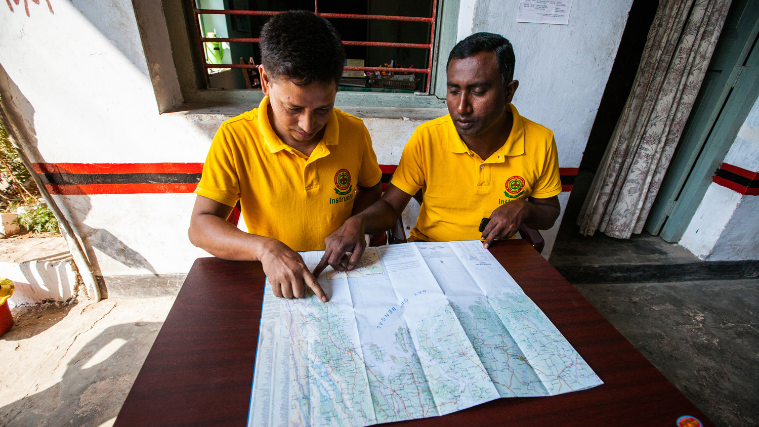 An RNLI instructor and a flood rescue trainee look at a map in Bangladesh