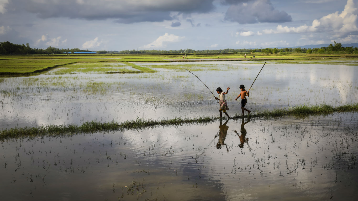 Reflections, brother and sister, Reshma (8) and Ridoy (9) are fishing on floodwaters in Cox's Bazaar, Bangladesh after a monsoon.