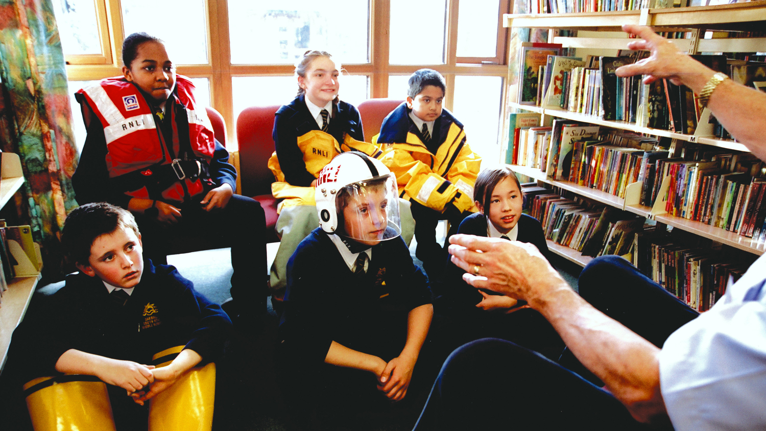 Young people learning about water safety from an RNLI education volunteer